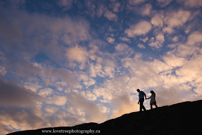 a couple set against a huge sky on the cliffs of west vancouver, shot by vancouver enagement photographers www.lovetreephotography.ca